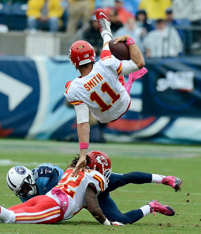 . Kansas City Chiefs quarterback Alex Smith (11) flips over Tennessee Titans cornerback Coty Sensabaugh (24) and Chiefs wide receiver Dexter McCluster (22) in the second quarter of an NFL football game on Sunday, Oct. 6, 2013, in Nashville, Tenn. (AP Photo/Mark Zaleski)