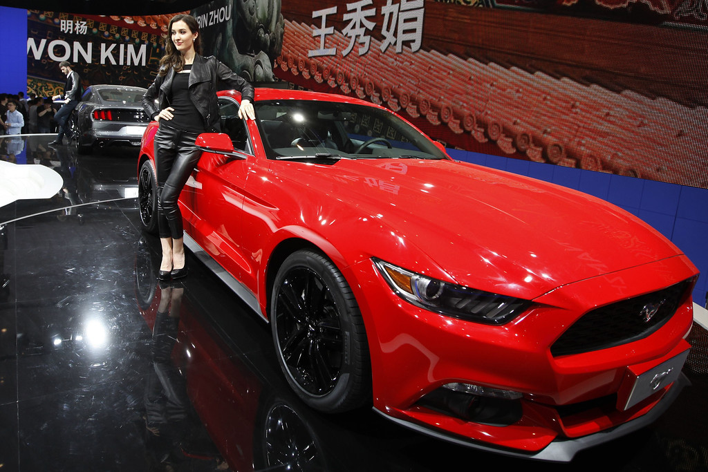 ". A model poses by a red Mustang 50th anniversary edition car on display at the China International Exhibition Center new venue during the ""Auto China 2014\"" Beijing International Automotive Exhibition in Beijing on April 21, 2014. AFP PHOTOSTR/AFP/Getty Images"