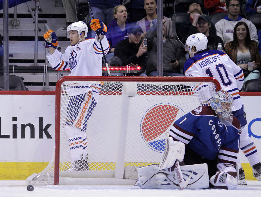 . Edmonton Oilers left wing Taylor Hall raises his arms after scoring a goal against Colorado Avalanche goalie Semyon Varlamov (1) in the first period of an NHL game on Friday, April 19, 2013, in Denver. Oilers center Shawn Horcoff (10) skates to Hall. (AP Photo/Joe Mahoney)