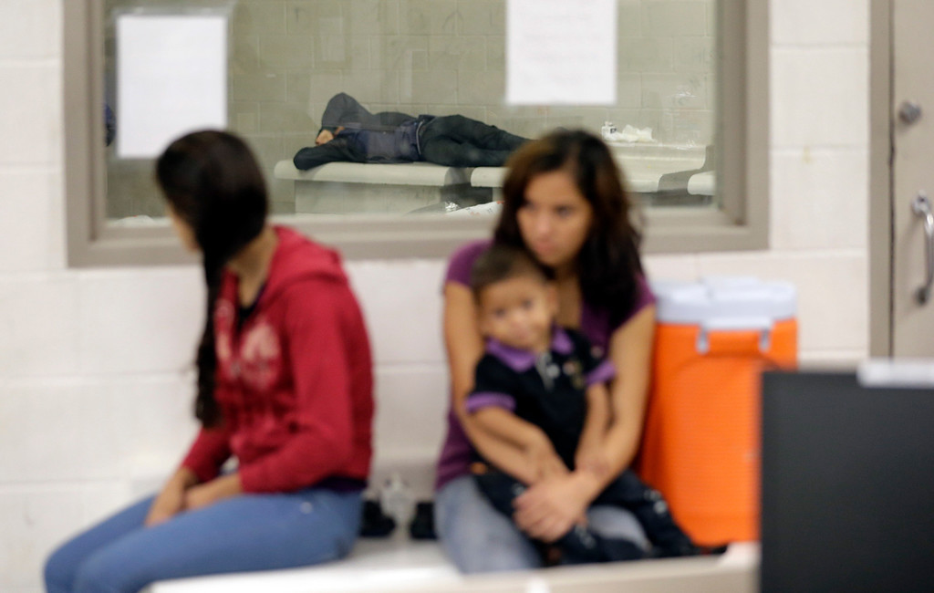 . Detainees wait at a U.S. Customs and Border Protection processing facility, Wednesday, June 18, 2014, in Brownsville,Texas.  (AP Photo/Eric Gay, Pool)