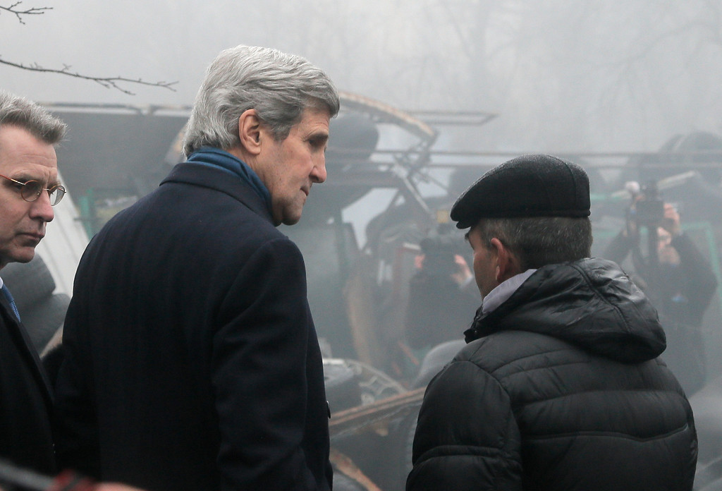 . U.S. Secretary of State John Kerry,left, speaks  with Ukrainian protester at  barricades in Kiev, Ukraine, Tuesday, March, 4, 2014. Secretary of State John Kerry flew to Kiev Tuesday to show U.S. support for the fledgling Ukraine government, and the Obama administration announced with his arrival a $1 billion energy subsidy package. (AP Photo/Efrem Lukatsky)