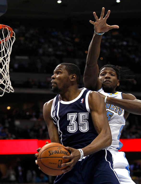 . Oklahoma City Thunder forward Kevin Durant (35) drives to the hoop past Denver Nuggets\' Kenneth Faried in their NBA basketball game in Denver March 1, 2013. REUTERS/Rick Wilking