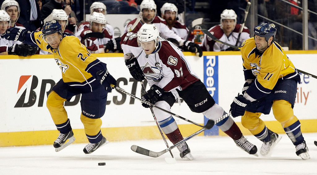 . Colorado Avalanche left wing Gabriel Landeskog (92), of Sweden, takes the puck between Nashville Predators right wing Patric Hornqvist (27), of Sweden, and center David Legwand (11) in the first period of an NHL hockey game Tuesday, April 2, 2013, in Nashville, Tenn. (AP Photo/Mark Humphrey)