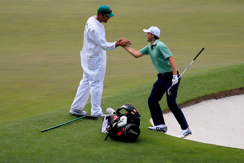 . Jordan Spieth of the United States celebrates with his caddie Michael Greller after holing out for birdie on the fourth hole during the final round of the 2014 Masters Tournament at Augusta National Golf Club on April 13, 2014 in Augusta, Georgia.  (Photo by Rob Carr/Getty Images)