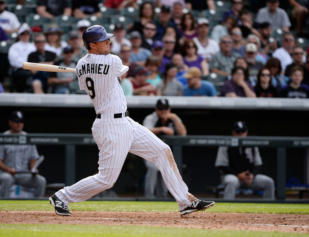 . Colorado Rockies second baseman, DJ LeMahieu, hits an RBI double to score teammates Drew Stubbs and Nolan Arenado, to take the lead in the 8th inning against the Chicago White Sox at Coors Field Wednesday afternoon, April 09, 2014. The Rockies went on to win 10-4. (Photo By Andy Cross / The Denver Post)