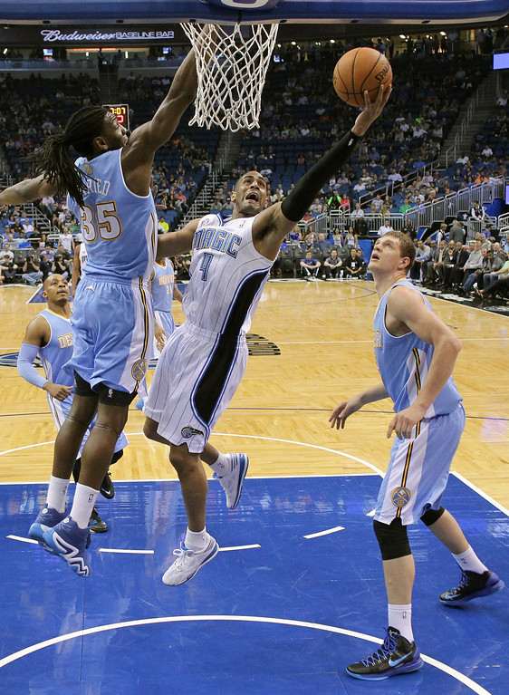 . Orlando Magic\'s Arron Afflalo (4) gets off a shot between Denver Nuggets\'s Kenneth Faried (35) and Timofey Mozgov, right, during the first half of an NBA basketball game in Orlando, Fla., Wednesday, March 12, 2014. (AP Photo/John Raoux)