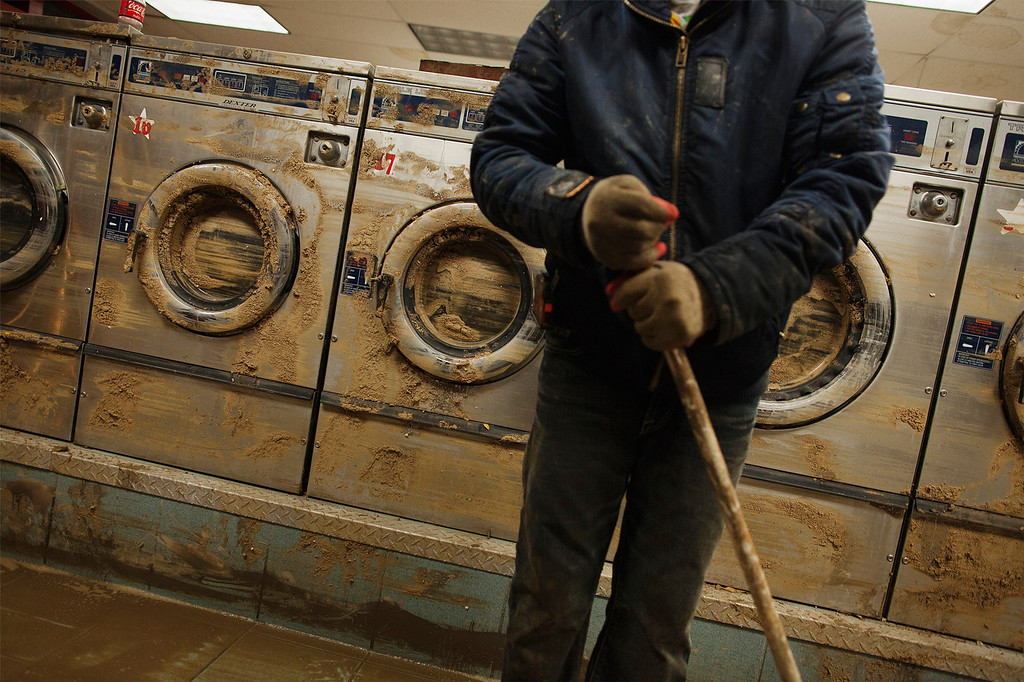 . Eddie Liu uses a broom to clean up mud and water from extensive flooding in a laundromat due to superstorm Sandy in the Coney Island neighborhood of New York November 2, 2012. Four days after superstorm Sandy smashed into the U.S. Northeast, rescuers on Friday were still discovering the extent of the death and devastation in New York and the New Jersey shore, and anger mounted over gasoline shortages, power outages and waits for relief supplies. REUTERS/Lucas Jackson
