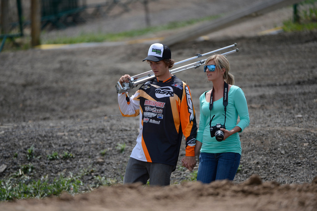 . LAKEWOOD, CO - MAY 23:  Local professional motocross rider, Derek Anderson, left, from Arvada Colorado, walks down the track with his girlfriend/team manager, Shialah Chavez after an interview during media day at the AMA Thunder Valley National at the Thunder Valley Motocross Park in Lakewood Colorado, Thursday May 23, 2013. The main AMA event is this Saturday at Thunder Valley. (Photo By Andy Cross/The Denver Post)