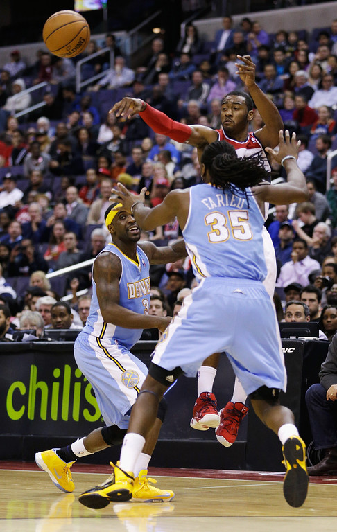 . WASHINGTON, DC - FEBRUARY 22: John Wall #2 of the Washington Wizards passes around Ty Lawson #3 and Kenneth Faried #35 of the Denver Nuggets during the second half at Verizon Center on February 22, 2013 in Washington, DC.  (Photo by Rob Carr/Getty Images)