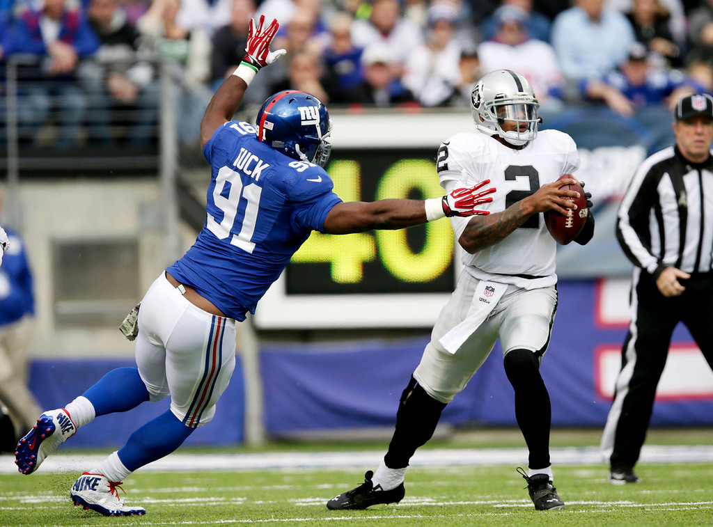 . Oakland Raiders quarterback Terrelle Pryor (2) tries to avoid New York Giants defensive end Justin Tuck (91) during the first half of NFL football game, Sunday, Nov. 10, 2013, in East Rutherford, N.J. (AP Photo/Kathy Willens)