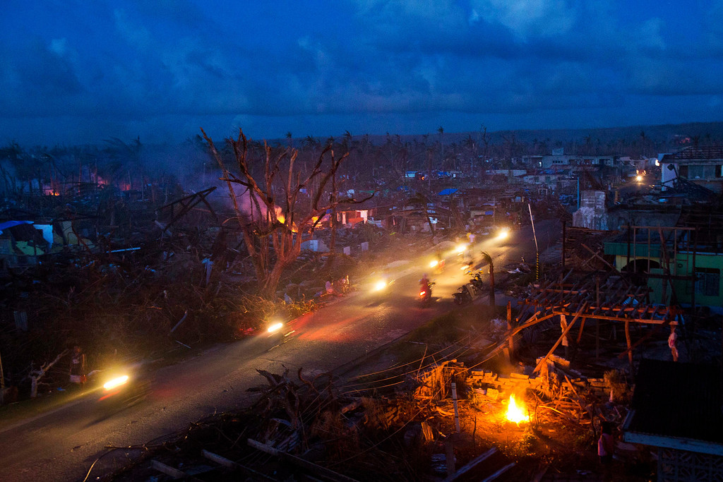 . Typhoon Haiyan survivors ride motorbikes through the ruins of the destroyed town of Guiuan, Philippines on Thursday, Nov. 14, 2013. Typhoon Haiyan, one of the most powerful storms on record, hit the country\'s eastern seaboard, destroying tens of thousands of buildings and displacing at least a half-million people.  (AP Photo/David Guttenfelder)