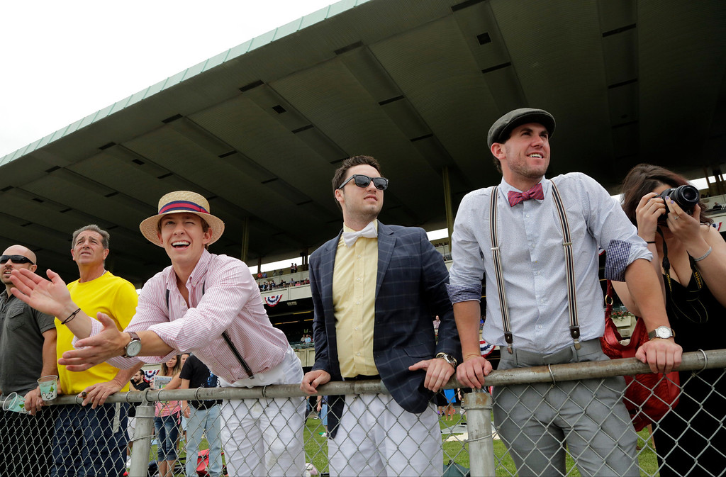 . Cody Dillabough, left, cheers as Chris Weidner, center and Brandon Engelhardt, right, watch the first race at Belmont Park Saturday, June 8, 2013 in Elmont, N.Y. A large field of 3-year-olds is set to run in the $1 million Belmont Stakes on Saturday. Among the competitors are Kentucky Derby winner Orb and Preakness winner Oxbow. (AP Photo/Mark Lennihan)