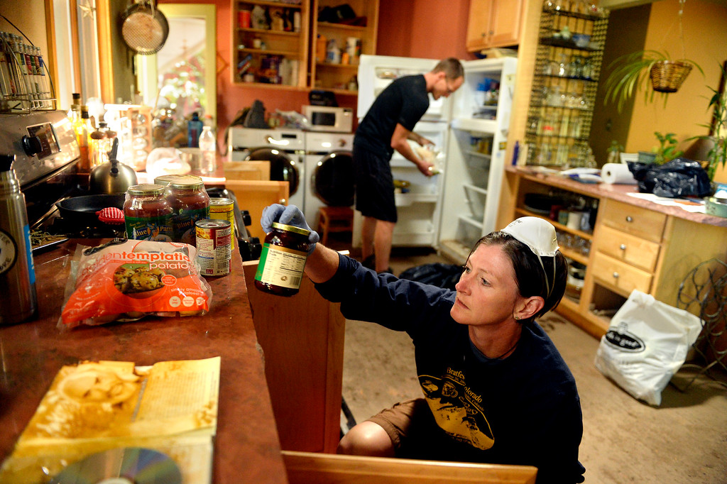 ". Brenna Willis cleans out cupboards at the home she shares with her partner Emma Birath in Lyons, CO September 20, 2013. She said they had 10 inches of water in the house and they were trying to salvage what they could.  Birath said, ""when we got here it was a bit of a shock. It looked worse than we thought. Water can do a lot of damage.\"" Friday was the second day residents were allowed to return to their homes.  (Photo By Craig F. Walker / The Denver Post)"