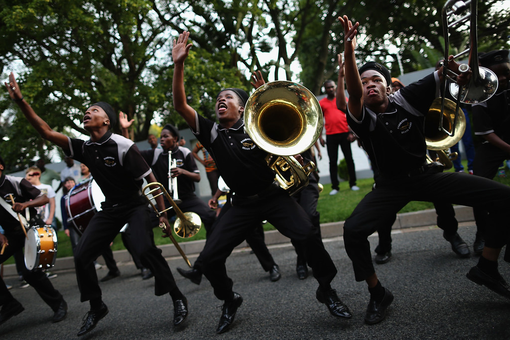 . A band plays outside the Houghton home of the former South African President Nelson Mandela on December 7, 2013 in Johannesburg, South Africa.  (Photo by Dan Kitwood/Getty Images)