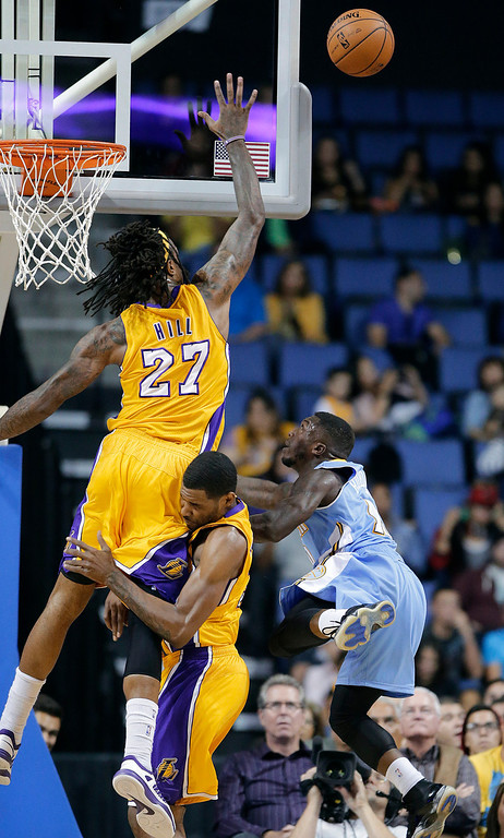 . Los Angeles Lakers\' Jordan Hill, top left, collides with Shawne Williams as he blocks a shot by Denver Nuggets\' Nate Robinson, right, in the first half of an NBA preseason basketball game Tuesday, Oct. 8, 2013, in Ontario, Calif. (AP Photo/Jae C. Hong)