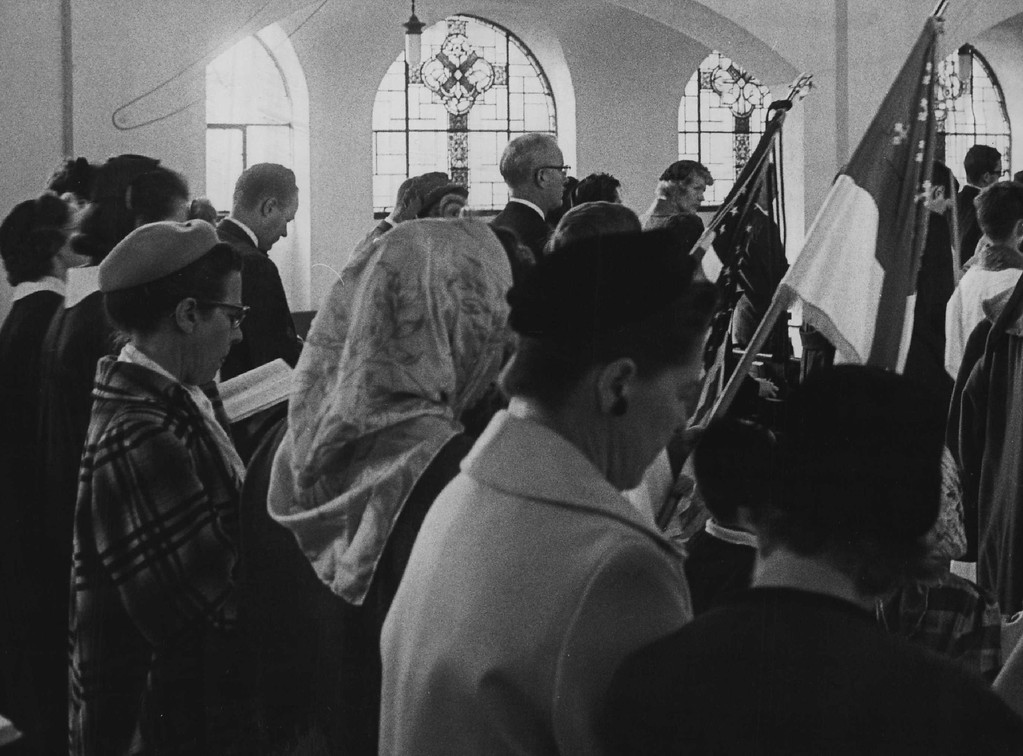 . Members of the congregation of Denver\'s St. Thomas Episcopal Church stand solemnly during Monday memorial services Nov. 25, 1963.