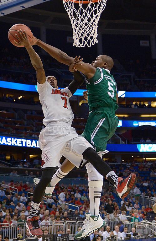 . Manhattan center Rhamel Brown (5) blocks a shot by Louisville guard Russ Smith (2) in a second-round game in the NCAA college basketball tournament Thursday, March 20, 2014, in Orlando, Fla.  (AP Photo/Phelan M. Ebenhack)