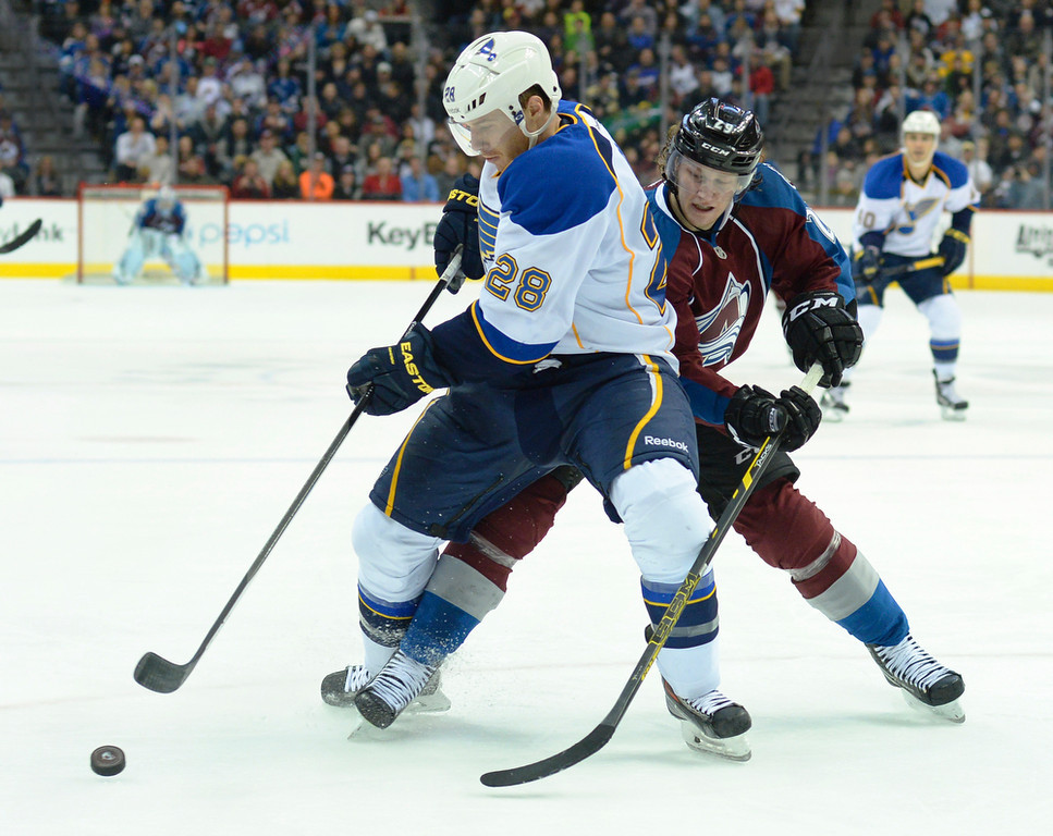 . Colorado center Nathan MacKinnon tried to take the puck from St. Louis defenseman Ian Cole (28) in the third period. The St. Louis Blues defeated the Colorado Avalanche 2-1 at the Pepsi Center Saturday afternoon, March 8, 2014 in Denver, Colorado. (Photo by Karl Gehring/The Denver Post)