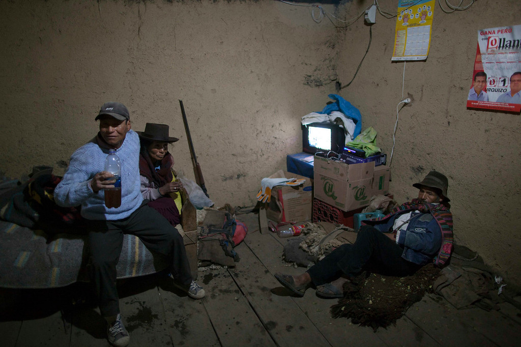 . Simeon Velasque, left, holds a plastic bottle filled with liquor as he sits with his wife, Aurora Saume, in Chaca, Peru. Velasque  joined earlier in the day other relatives of villagers slain by insurgents nearly three decades ago to formally bury the remains the victims, including his father, exhumed last year from a common grave in the remote Ayacucho state hamlet. No state agency exists dedicated to locating and cataloguing the conflict\'s estimated 15,000 disappeared. The bodies of fewer than 3,000 have been exhumed.   (AP Photo/Rodrigo Abd)
