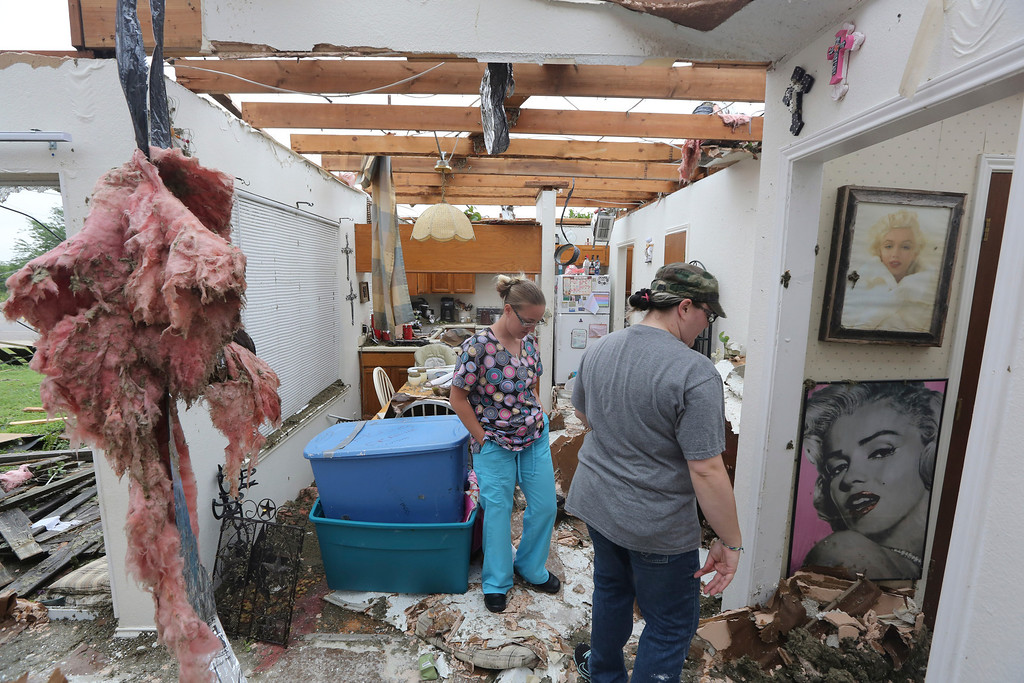 . People look at damage as they help to start cleaning up and salvage items from a home that was destroyed by a tornado in Cleburne, Texas, Thursday, May 16, 2013. (AP Photo/LM Otero)