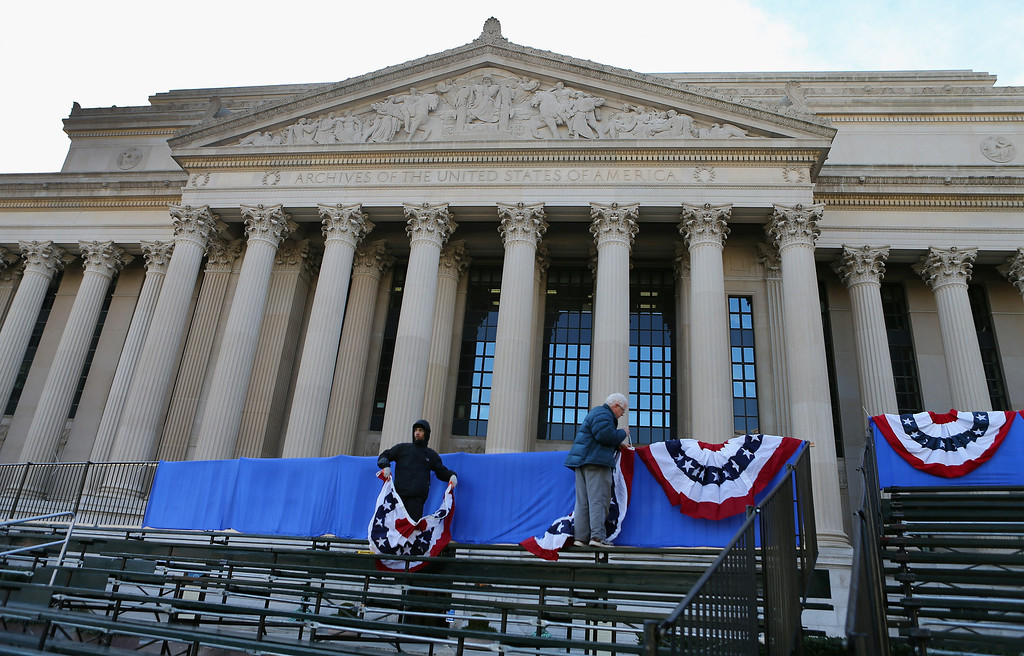 . Workers hang bunting along the bleachers along Pennsylvania Ave as preparations continue for the Inauguration Parade on January 20, 2013 in Washington, DC.  The US capital is preparing for the second inauguration of US President Barack Obama, which will take place on January 21.  (Photo by Joe Raedle/Getty Images)