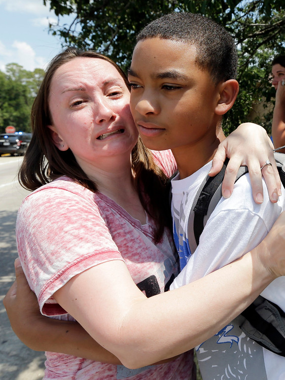 . Lora Ross, left, hugs her son Jonathan Ross outside Spring High School Wednesday, Sept. 4, 2013, in Spring, Texas. Students were dismissed after a 17-year-old student was stabbed to death and three others were injured in a fight at the Houston-area high school. (AP Photo/David J. Phillip)