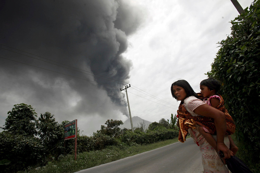 . A woman and her daughter flee their home as Mount Sinabung erupts in Karo, North Sumatra, Indonesia, Tuesday, Sept. 17, 2013. Thousands of people were evacuated from their villages following the eruption the 2,600-meter (8,530-feet) volcano Sunday after being dormant for three years, sending thick ash into the sky with small rocks pelting neighboring villages.   (AP Photo/Binsar Bakkara)