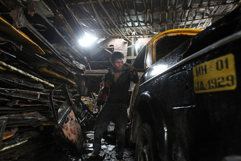 . In this Tuesday, July 30, 2013, an Indian worker dismantles a Mumbai Premier Padmini taxi in a scrapyard, in Mumbai, India. More than 4500 Premier Padmini taxis are expected to be banned from the roads in Mumbai this year, starting in August,  in line with a government order that bans cabs that are more than 20 years old. (AP Photo/Rafiq Maqbool)