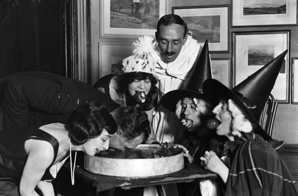 . October 1922:  An apple bobbing game at a Halloween fancy-dress party.  (Photo by Topical Press Agency/Getty Images)
