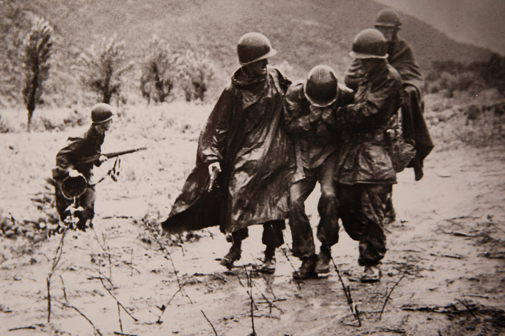 . One of the two iconic photographs of Father Emil Kapaun shows him on the left, and Capt. Jerome A. Dolan, a medical officer with the 8th Cavalry regiment, on the right, carrying an exhausted GI off a battlefield in Korean, early in the war. Father Emil Kapaun will be awarded the Medal of Honor on April 11, 2013. (Catholic Diocese of Wichita/Wichita Eagle/MCT)