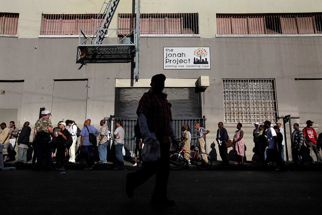. People form a line to get a free hotdog from a charity organization in the Skid Row area of Los Angeles on Tuesday, July 23, 2013. (AP Photo/Jae C. Hong)