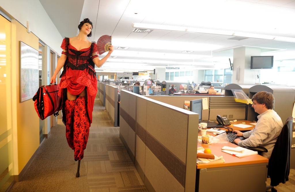 Description of . DENVER,CO. - APRIL 4:  This is my best behind the scenes moment as stilt performer Alexis Scissor Legs aka Danielle Hendricks strolls nonchalantly through the newsroom of The Denver Post on Thursday, April 4,  2013 while headed to a video interview in the photo department.  She actually managed to climb into the elevator with her stilts.  (Photo By Cyrus McCrimmon/The Denver Post)