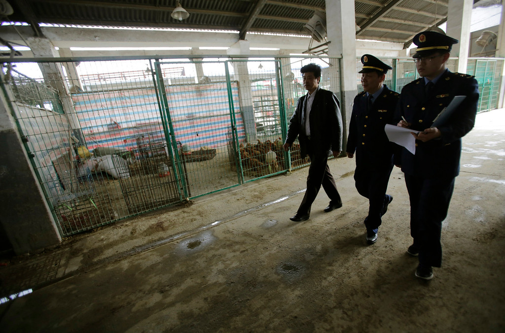 . Inspectors from the city\'s commercial and industry bureau review a chicken wholesale market on Wednesday, April 3, 2013, in Shanghai, China. Scientists taking a first look at the genetics of the bird flu strain that recently killed two men in China said Wednesday the virus could be harder to track than its better-known cousin H5N1 because it might be able to spread silently among poultry without notice. The virus also appears to have mutated into a form that enables it to more easily infect animals such as pigs, meaning they could serve as hosts that spread the virus more widely among humans. (AP Photo/Eugene Hoshiko)