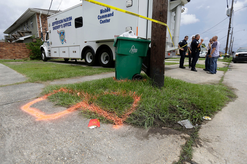 . Police stand near spray paint markings of trash bins, where the body of missing 6-year-old Ahlittia North was found in Harvey, La., Tuesday, July 16, 2013, according to Lisa North, the child\'s mother. North says Jefferson Parish authorities told her they have found the body of her daughter in a Harvey trash bin. Ahlittia disappeared from her apartment late Friday night or early Saturday morning. North\'s husband Albert Hill said they were told the body was found in a trash bin not far from their apartment. (AP Photo/Gerald Herbert)