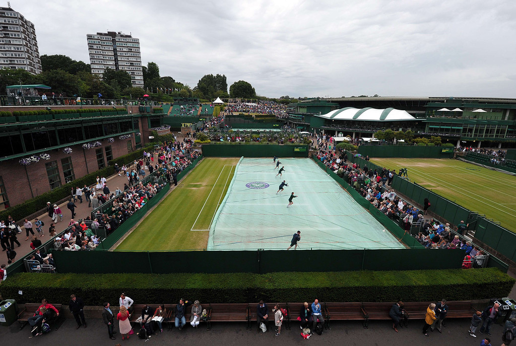 . Ground staff uncover an outer court after rain interrupted play on day eight of the 2013 Wimbledon Championships tennis tournament at the All England Club in Wimbledon, southwest London, on July 2, 2013. CARL COURT/AFP/Getty Images