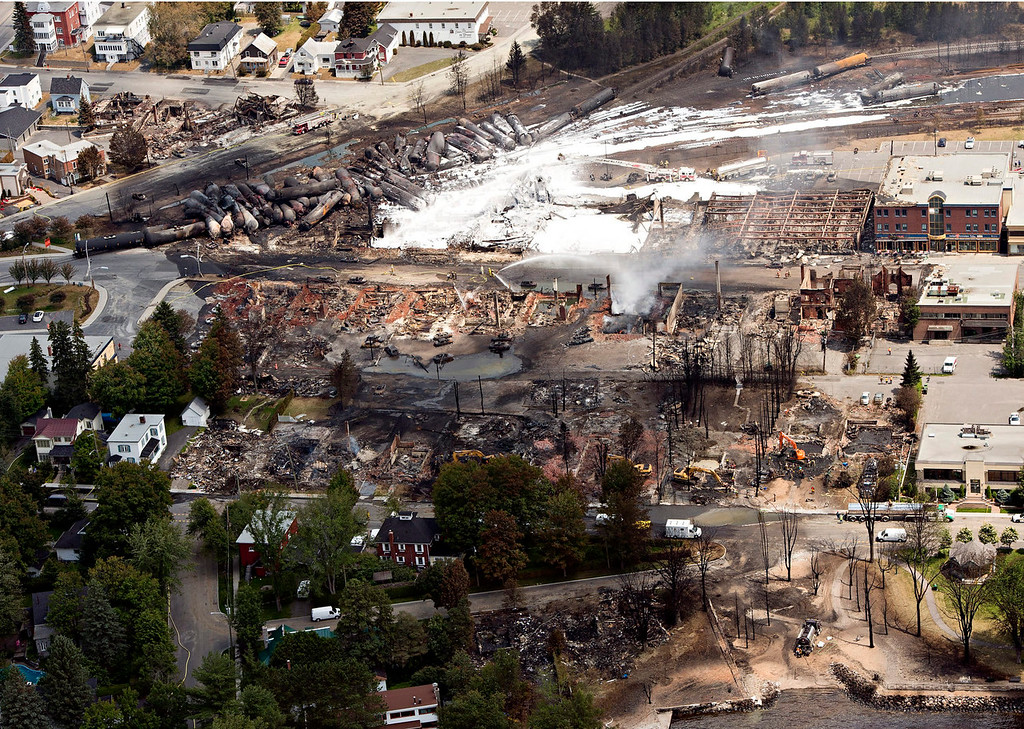 . The downtown core lays in ruins as fire fighters continue to water smoldering rubble Sunday, July 7, 2013 in Lac Megantic, Quebec.  A runaway train derailed  Saturday igniting tanker cars carrying crude oil.