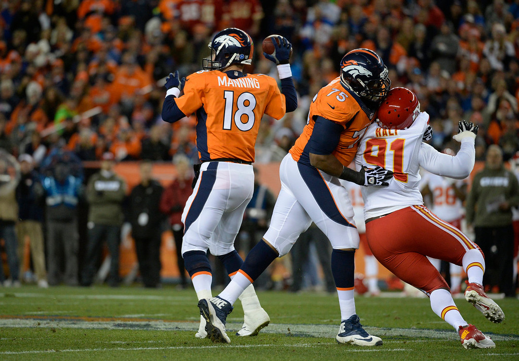 . Denver Broncos tackle Chris Clark (75) stops Kansas City Chiefs outside linebacker Tamba Hali (91) from reaching Denver Broncos quarterback Peyton Manning (18) as he makes a pass in the first quarter. The Denver Broncos take on the Kansas City Chiefs at Sports Authority Field at Mile High in Denver on November 17, 2013. (Photo by Tim Rasmussen/The Denver Post)