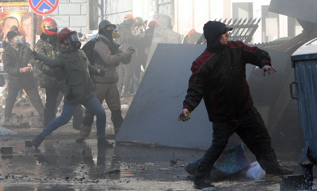 . Protester throw stones to riot police during an anti-government protest in downtown Kiev, Ukraine, 18 February 2014.   EPA/IGOR KOVALENKO