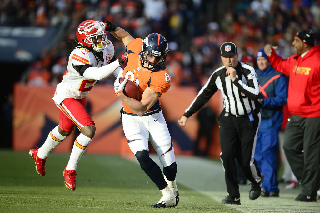. Denver Broncos tight end Joel Dreessen (81) tries to avoid the sidelines as he\'s tackled by Kansas City Chiefs free safety Kendrick Lewis (23) as the Denver Broncos took on the Kansas City Chiefs at Sports Authority Field at Mile High in Denver, Colorado on December 30, 2012. AAron Ontiveroz, The Denver Post