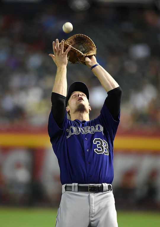 . Justin Morneau #33 of the Colorado Rockies catches a pop fly just behind first base during the third inning against the Arizona Diamondbacks at Chase Field on August 8, 2014 in Phoenix, Arizona.  (Photo by Norm Hall/Getty Images)