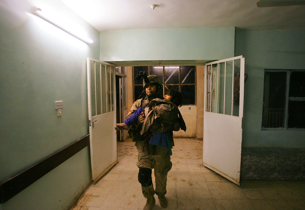 . Racan Hassan, 11, is carried by hospital staff after being shot by U.S. soldiers of the 25th Infantry Division January 18, 2005 in Tal Afar, Iraq. The troops fired on the Hassan family car when it unwittingly approached them during a dusk patrol in the tense northern Iraqi town. Parents Hussein and Camila Hassan were killed instantly, and their son Racan was seriously wounded in the abdomen. Racan, who lost the use of his legs, was treated later in the U.S.  (Photo by Chris Hondros/Getty Images)