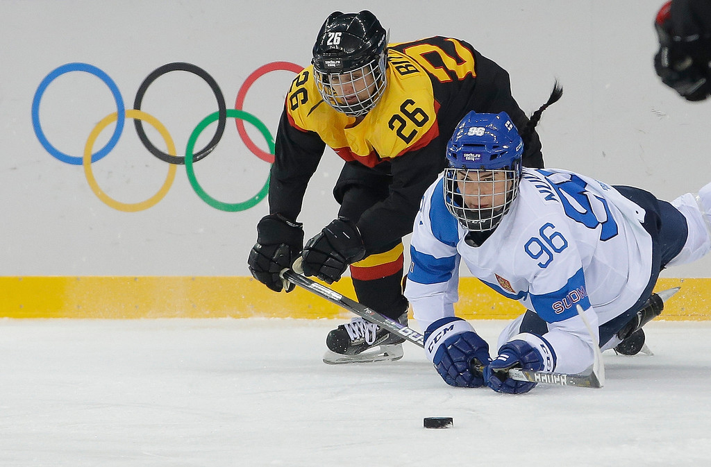 . Monika Bittner of Germany and Emma Nuutinen of Finland chase a chase a loose puck during the 2014 Winter Olympics women\'s ice hockey game at Shayba Arena, Sunday, Feb. 16, 2014, in Sochi, Russia. (AP Photo/Matt Slocum)