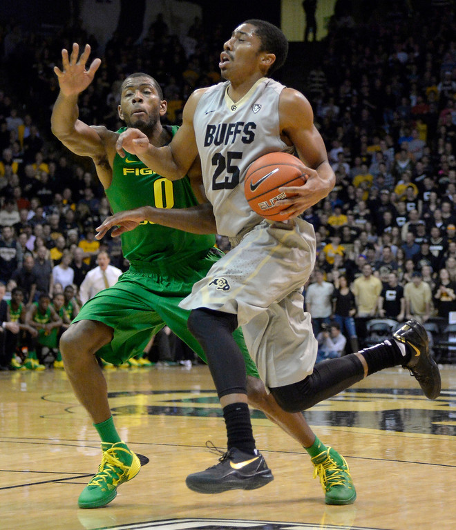 . Colorado Buffaloes guard Spencer Dinwiddie (25) drives on Oregon Ducks forward Mike Moser (0) during the second half  January 5, 2014 at Coors Events Center. (Photo by John Leyba/The Denver Post)
