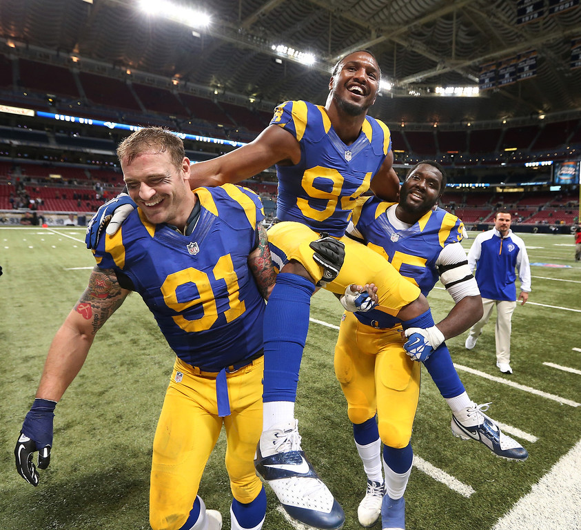. St. Louis Rams defensive end Robert Quinn is carried off the field by fellow defensive ends Chris Long, left, and William Hayes after setting the franchise single-season sack record at 18, following an NFL football game against the Tampa Bay Buccaneers on Sunday, Dec. 22, 2013, in St. Louis. The Rams won 23-13. (AP Photo/St. Louis Post-Dispatch, Chris Lee)