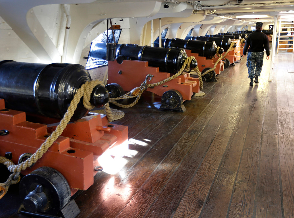 . A U.S. Navy sailor walks past a row of guns aboard the USS Constitution, in Boston, Monday, Sept. 30, 2013. The USS Constitution, an 18th century naval warship, is among prominent Boston-area historic sites that would be affected Tuesday should a partial shutdown of the federal government occur at midnight. (AP Photo/Steven Senne)