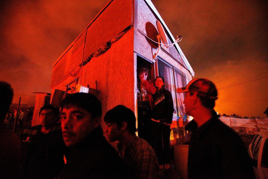 . People gather at a street corner as the scene is illuminated by the glow of encroaching forest fires in Valparaiso, Chile, Sunday April 13, 2014. Authorities say the fires have destroyed hundreds of homes, forced the evacuation of thousands and claimed the lives of at least seven people.  ( AP Photo/ Luis Hidalgo)