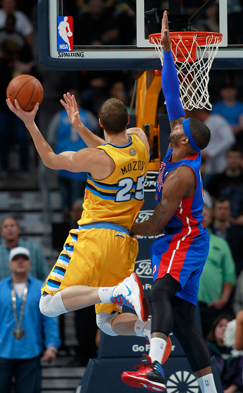 . Denver Nuggets center Timofey Mozgov, left, of Russia, goes up for shot as Detroit Pistons forward Josh Smith covers in the first quarter of an NBA basketball game in Denver on Wednesday, March 19, 2014. (AP Photo/David Zalubowski)