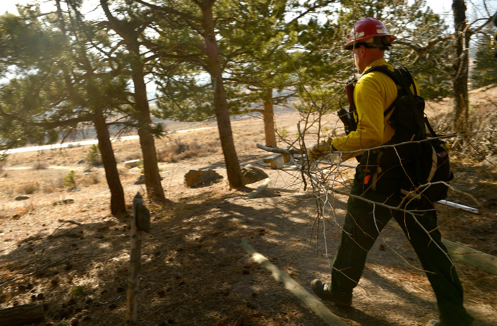 . Wildland firefighter Mark Murray, from Lafayette Fire, clears brush and debris from the Moraine Park Vistor\'s Center to protect the structure just in case the fire reaches the building on December 2nd, 2012. The Fern Lake Fire, which has been burning in Rocky Mountain National Park since October, kicked up yesterday and forced the evacuation of hundreds of homes east of the fire. Helen H. Richardson, The Denver Post