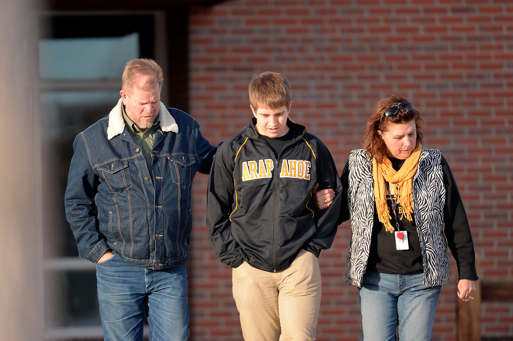 . CENTENNIAL, CO - Sam Gardinier, Jr at Arapahoe High School leaves Euclid Middle School with his parents Tom and Chris Gardinier after getting bused their from Arapahoe High School December 13, 2013. A gunman at the school was targeting a teacher at the school. The gunman shot two students in the process and then turned the gun on himself. (Photo by John Leyba/The Denver Post)