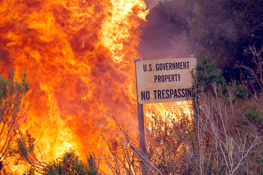 . A brush fire burns a sign at a shooting range on the beach at Navel Base Ventura County on Friday, May 3, 2013.  Santa Ana winds that sent a Southern California wildfire barreling to the sea have died but flames are still running through coastal canyons, threatening scattered homes and wilderness. (AP Photo/Nick Ut)